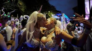 A female couple in silver bikinis, one with a unicorn horn, kiss during the annual Sydney Gay and Lesbian Mardi Gras festival in Sydney, Australia March 4, 2017.