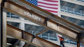 Contractor walks on a steel beam