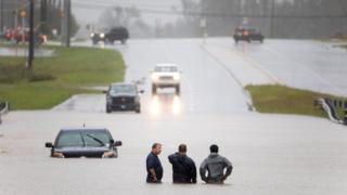 Men stand waist-deep in water, as a car is submerged heavily in Holly Ridge, North Carolina