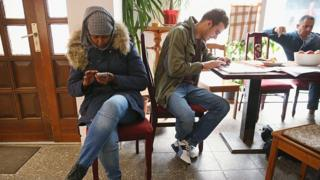 Warda Abdi (L), 23, an asylum-seeker from Somalia, at an internet cafe in Bad Belzig, Germany, on 26 October 2015