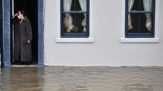A resident of York stands on her doorstep beside a flooded street