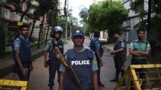 Bangladeshi policemen guard a check-point on a road block leading to the Holey Artisan Bakery, the scene of a fatal attack and siege, in Dhaka on July 3, 2016