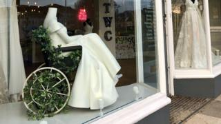 The White Collection of their bridal shop window in North Somerset with a mannequin in a wheelchair