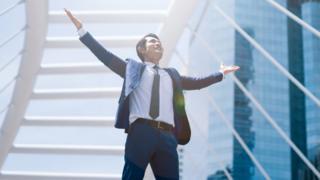 Un ejecutivo alza los brazos en señal de triunfo.