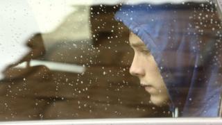 Teenage boy in through car window