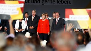German Chancellor Angela Merkel (C) and other party members sing the national anthem after addressing an election campaign rally of the Christian Democratic Union (CDU) in Bitterfeld, eastern Germany