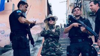 Madonna poses with military police wielding guns in a Rio de Janeiro slum.