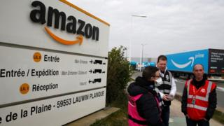 Workers stand outside an Amazon depot in France