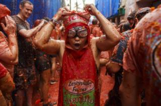 Revellers enjoy the atmosphere in tomato pulp while participating the annual Tomatina festival on 30 August 2017 in Bunol, Spain.