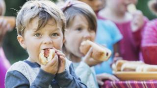 Niños comiendo perros calientes.