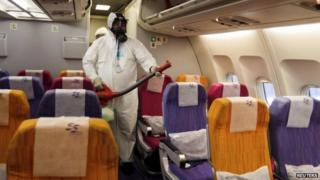 An official disinfects the cabin of an aircraft at Bangkok's airport