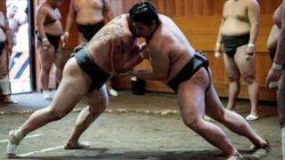 In this picture taken on August 28, 2019, sumo wrestlers try to push each other out of the ring