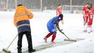 A player at Peterborough United sweeping the pitch