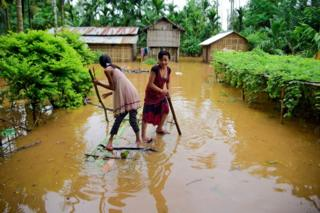 Girls row a makeshift raft past submerged houses at a flood-affected village in Assam's Karbi Anglong district.
