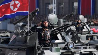 Korean People's Army (KPA) soldiers stand atop armoured vehicles during a military parade