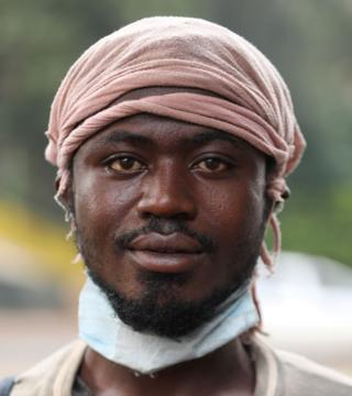 A Burundian refugee Bazira Afros, 26yrs old, who fled his country due to election violence, poses for a photo next to a footbridge where he and other refugees sleep next to a highway, ahead of World Refugee Day in Nairobi, Kenya, 19 June 2020.
