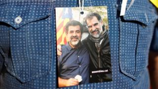 A supporter of Catalan independence holds a picture of two leaders of Catalan separatist groups, Jordi Sanchez and Jordi Cuixart