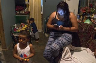 Greicy looks at her mobile phone while her son and her nephew play