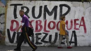 """Un hombre y una mujer pasan frente a un muro con una pancarta que lee: """"Trump desbloquea Venezuela"""""""