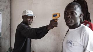 A health worker monitors the temperature of a traveller from the DR Congo