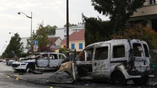 Burned-out police vehicle (L) in Viry-Chatillon, near Paris (8 October)