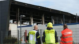 Firemen and an emergency services worker stand outside a sports hall struck by fire that was intended to house refugees and migrants applying for asylum in Germany on 25 August 2015 in Nauen