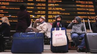 commuters at station with trains cancelled and delayed