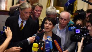 Frauke Petry with many microphones pointing at her, and supporters by her side