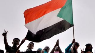 Sudanese demonstrators wave the national flag as they attend a protest rally