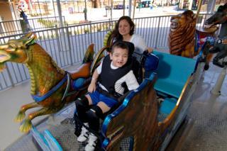 A young boy in a wheelchair enjoys the carousel