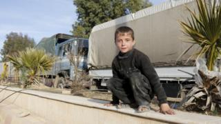 A boy plays near aid convoys in a rebel-held Syrian town