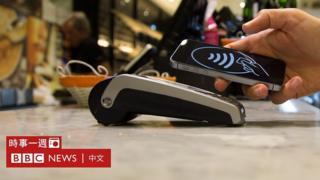 一家麵包店內顧客用手機付款(資料圖片)