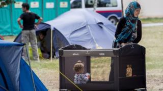 A refugee mother guards her baby in the grounds of the Traiskirchen camp