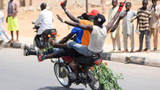 Supporters of Nigeria's President Muhammadu Buhari gesture on a motorbike as they celebrate in Katsina, Nigeria - 27 February 2019