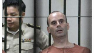 Christopher Paul Neil, right, sits next to a Thai prison official at criminal court in Bangkok, Thailand Monday, March 10, 2008. Neil was arrested in Thailand on Oct. 19, 2007 after Interpol had issued an unprecedented global appeal