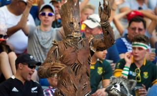 Two persons dressed as Groot (L) and Rocket Raccoon from Guardians of the Galaxy react during the World Rugby Sevens Series semi-final match England vs Scotland, on December 11, 2016, in Cape Town