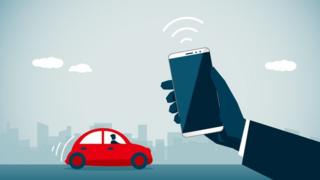 Phone being held up in front of a car