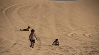 Children play in the dunes