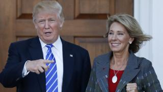 Donald Trump and Betsy DeVos pose for photos at Trump National Golf Club in Bedminster, New Jersey