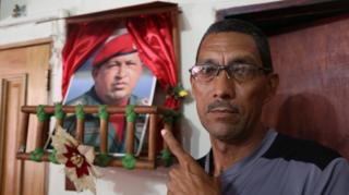 Marcos Lobos points to a shrine to the late president, Hugo Chávez, in his home