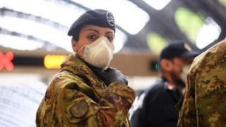 A female member of Italy's military looks as police check people at Milan's main railway station. Photo: 9 March 2020