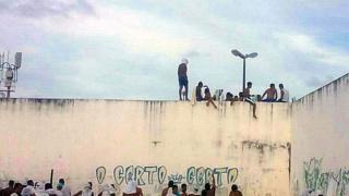 Presos sobre el muro de la cárcel de Alcaçuz, en Río Grande del Norte, Brasil.