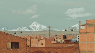 Casas com tijolo aparente e sem pintura e, em segundo plano, as cordilheiras dos Andes com gelo