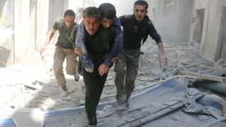 Rescue workers carry civilians out of a building following a reported government air strike in Aleppo, Syria (29 April 2016)