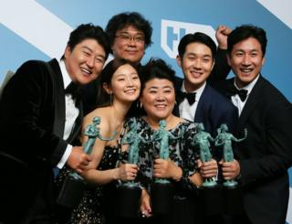 Director Bong Joon-ho stands behind the cast of Parasite