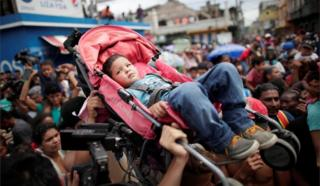 Honduran migrants hold up a child in a buggy while gathering at the Guatemalan border
