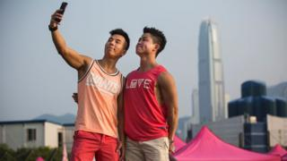 A couple take a 'selfie' at Pink Dot, a lesbian, gay, bisexual, transgender/transsexual and intersex (LGBTI) carnival in the West Kowloon district of Hong Kong on September 25, 2016. Pink Dot, 2016, is a free carnival co-organised by BigLove Alliance and Pink Alliance for friends, family and colleagues of the LGBTI community that celebrates inclusivity and diversity.