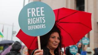 """A woman holds a slogan that reads """"Free rights defenders"""" outside Istanbul's court. Photo: 25 October 2017"""