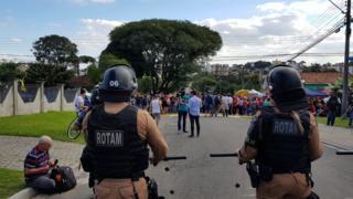 Dois PMs fazem segurança de área da PF em Curitiba; ao fundo, uma fita amarela delimita a área de segurança; atrás da fita, há manifestantes