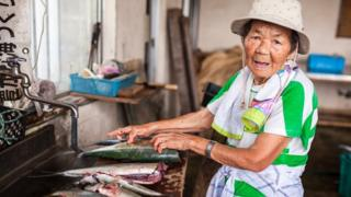 Idosa japonesa limpa peixes